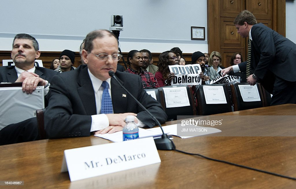 Acting Director of the Federal Housing Finance Agency, the conservator for Fannie Mae and Freddie Mac, Edward J. DeMarco (seated) pauses his testimony as an aide ¨ tries to take away placards from demonstrators in the background during a hearing on 'Sustainable Housing Finance' before the House Financial Services Committee in Washington, DC, March 19, 2013. AFP PHOTO/Jim WATSON