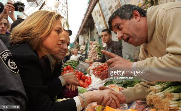 Acting Israeli Foreign Minister Tzipi Livni and second on the Kadima list speaks to a vendor 27 March 2006 during an elections visit to a local...