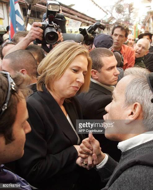 Acting Israeli Foreign Minister Tzipi Livni and second on the Kadima list speaks with an Israeli as she walks through a local market in Jerusalem 27...