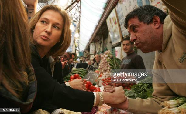 Acting Israeli Foreign Minister Tzipi Livni and second on the Kadima list shakes hands with a vendor 27 March 2006 during an elections visit to a...
