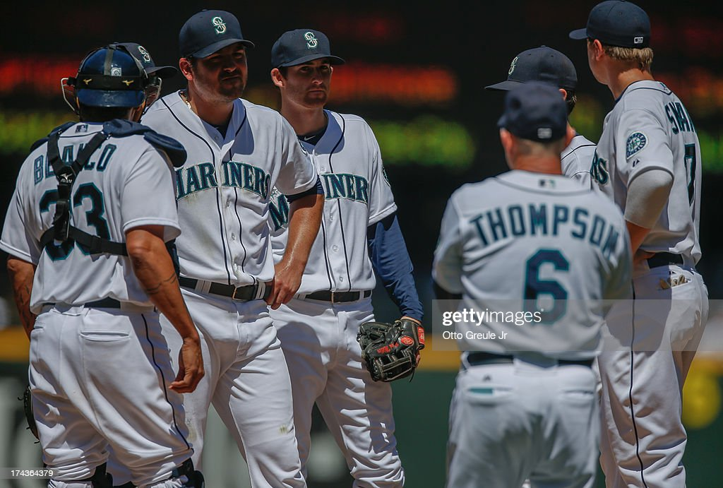 Acting manager Robby Thompson #6 of the Seattle Mariners heads to the mound to remove starting pitcher Joe Saunders #23 (2L) in the fifth inning against the Cleveland Indians at Safeco Field on July 24, 2013 in Seattle, Washington.