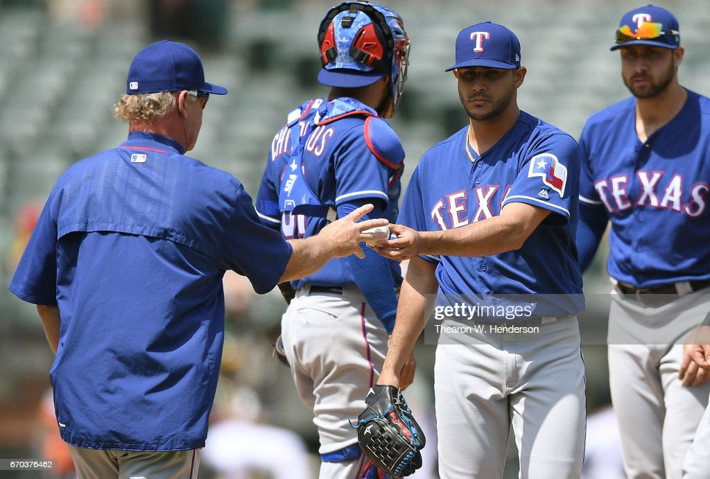 Acting manager Steve Buechele #24 of the Texas Rangers takes the ball from starting pitcher Martin Perez #33 against the Oakland Athletics in the bottom of the fourth inning at Oakland Alameda Coliseum on April 19, 2017 in Oakland, California.