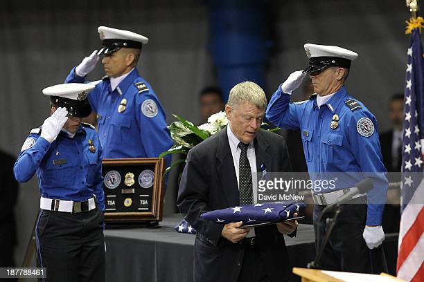 Acting Secretary of the US Department of homeland Security Rand Beers carries a US flag to present to Ana Hernandez widow of Transportation Security...