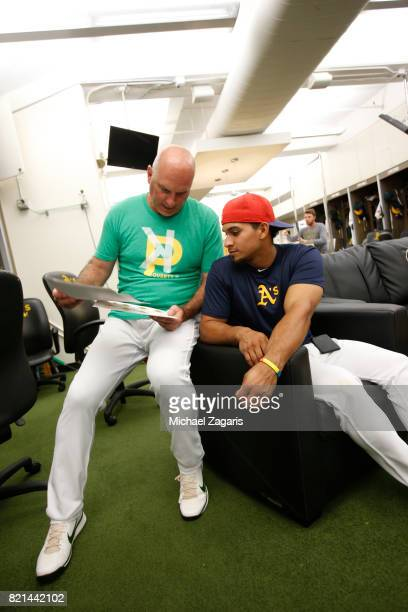Acting Third Base Coach Steve Scarsone and Franklin Barreto of the Oakland Athletics talk in the clubhouse prior to the game against the Chicago...