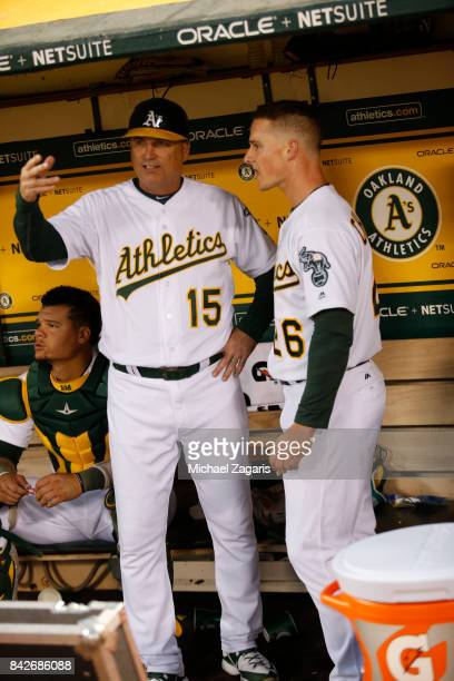 Acting Third Base Coach Steve Scarsone and Matt Chapman of the Oakland Athletics talk in the dugout during the game against the Kansas City Royals at...