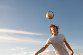 Male soccer player jumping up to head the ball.