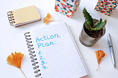 action plan written in notebook on white table