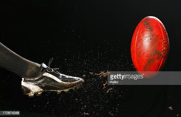 Action shot AFL kick with dirt movement and red ball
