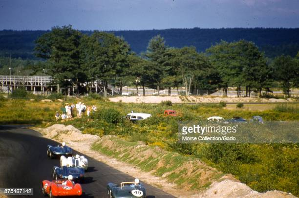 Action view of sports cars cruising at speed along the track at the SCCA National Races in Montgomery New York August 17 1958 At center spectators...