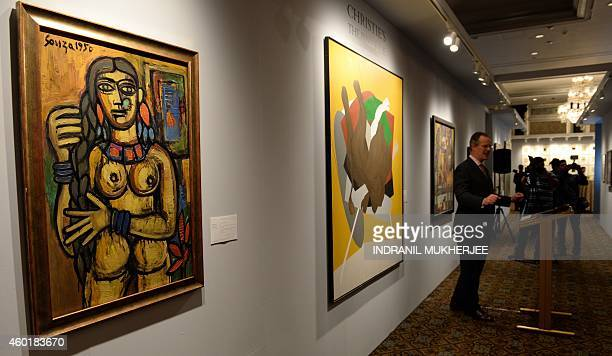 Actioneer William Robinson speaks next to Francis Newton Souza's 'FrontBack Nude' and Tyeb Mehta's 'Untitled ' during a media preview ahead of...