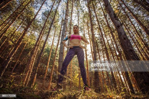 Active and sporty woman standing in autumn nature