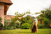 Active childhood - little child making handstand outside in backyard