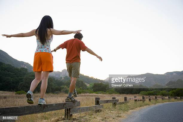 Active couple balancing on low fence.