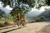 Active couple biking on scenic road.
