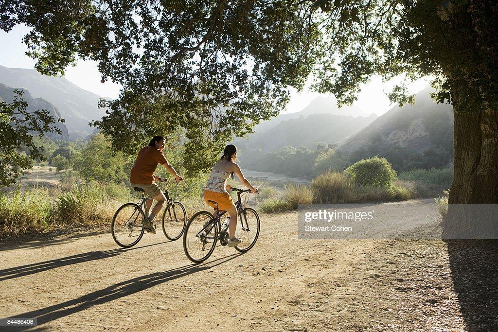 Active couple biking on scenic road. : Stock Photo
