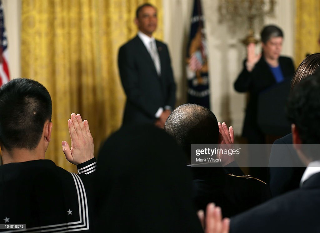 Active duty service members hold up thier hands while U.S. President Barack Obama listens to Homeland Security Secretary Janet Napolitano administer the oath of allegiance during a naturalization ceremony in the East Room of the White House on March 25, 2013 in Washington DC. Napolitano administered the oath of allegiance to active duty service members and civilians officially granting them United States citizenship.