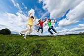 Mother and kids jumping outdoor against blue sky