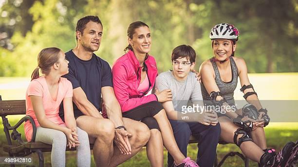 Aktive Familie sitzt auf einem park bench
