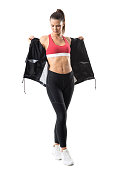 Active fit woman in leggings taking off tracksuit jacket showing abs. Full body length portrait isolated on white background.