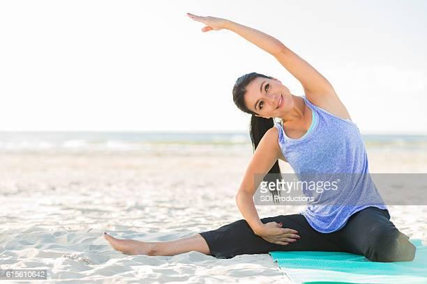 Active Hispanic woman does yoga at the beach