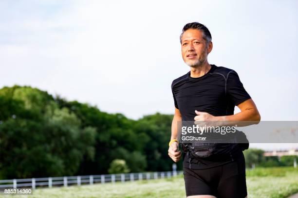 太陽の光に対してジョギング アクティブ シニア男性