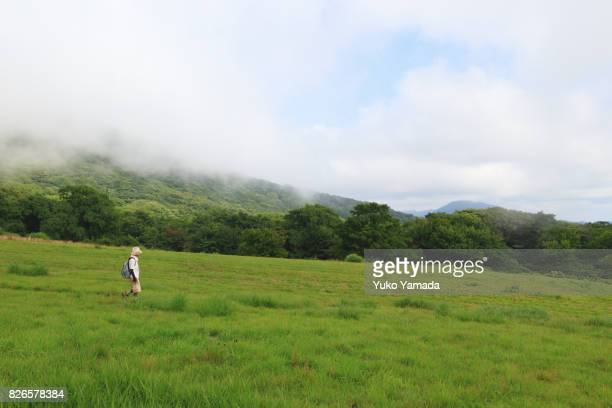Active Japanese Senior Woman Going Down Gently Sloping Hill