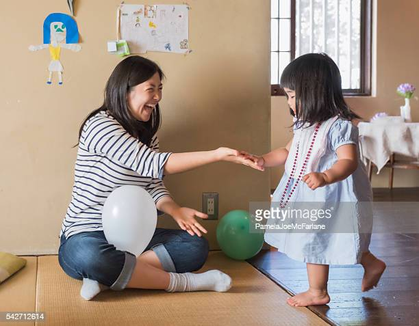 Active Japanese Toddler Girl Slapping Hands with Older Sister