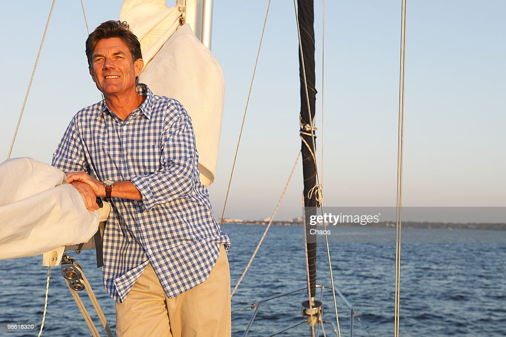 Active man relaxing on deck of sailboat at sunset.