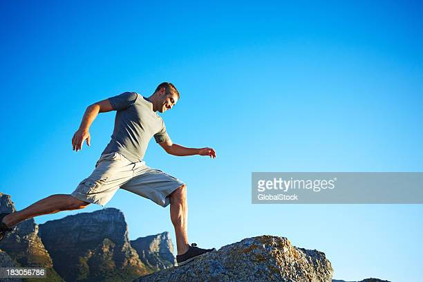 Active man running over rocks against blue sky with copyspace