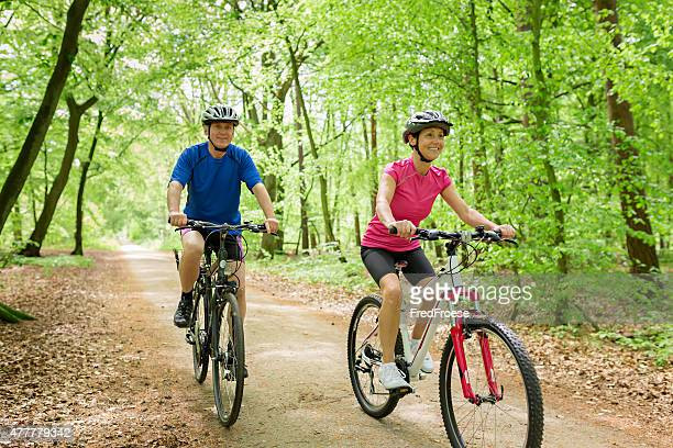 Active mature couple outdoors riding bikes in the nature