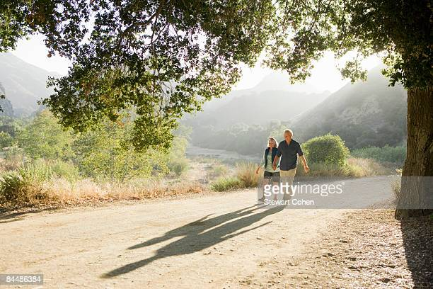 Active mature couple walking down scenic road