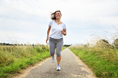 active mature woman jogging outdoors