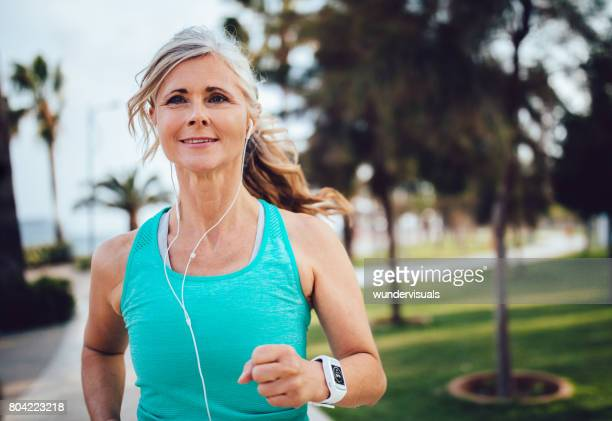 Actieve volwassen vrouw met hoofdtelefoons en smartwatch uitgevoerd in park