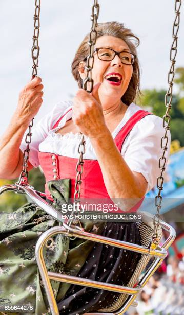 Active retired senior woman in traditional Bavarian dirndl dress has great fun visiting the Oktoberfest in Munich.
