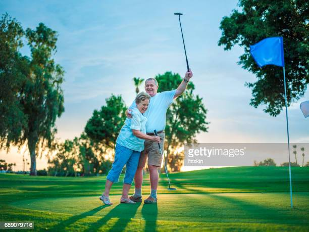 Active senior couple playing golf