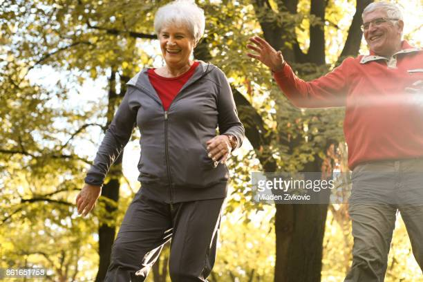 Active senior couple together in park having fun.