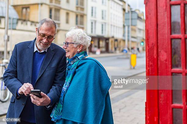 Active Senior Couple Using a Mobile Phone in England