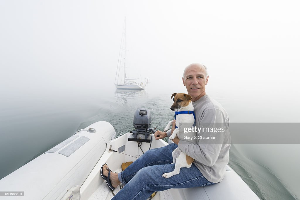 Active senior heads to shore with pet dog : Stock Photo