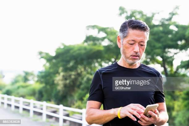 アクティブ シニア日本男ログをジョギングにスマート フォンをチェック