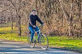 Active senior man outdoors riding his bike. Nature.