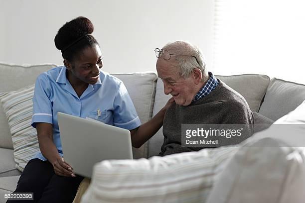 Un homme senior à l'aide d'ordinateur portable avec la femme carer à la maison