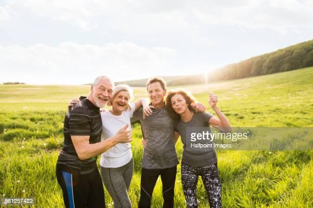 Active senior runners in nature taking photo.