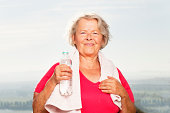 active senior woman after training with bottle of water