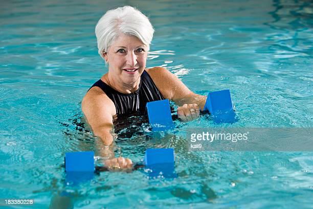 Active senior woman doing water aerobics