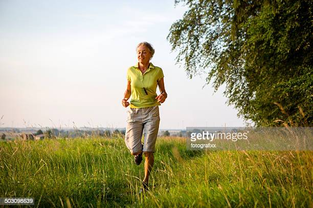 active senior woman is jogging outdoors