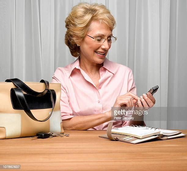 Active senior woman texting