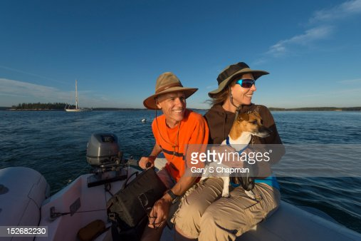 Active seniors dinghy to shore from sailboat : Foto de stock
