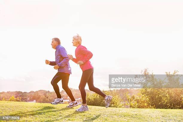 Active seniors running, exercising outdoors.