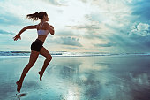Active sporty woman run along ocean surf by water pool to keep fit and health. Sunset black sand beach background with sun. Woman fitness, jogging workout and sport activity on summer family holiday.