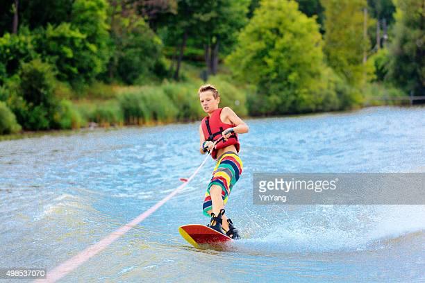 Active Teen Boy Water Ski Boarding on Lake in Summer